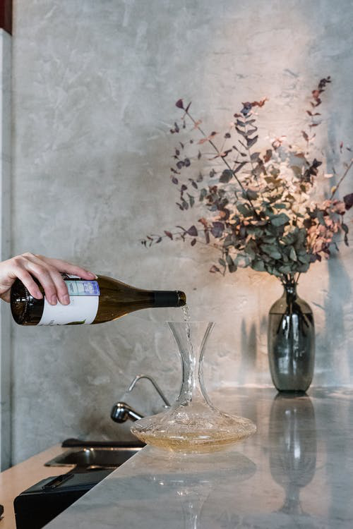 A person is pouring white wine in a crystal decanter to aerate the drink.