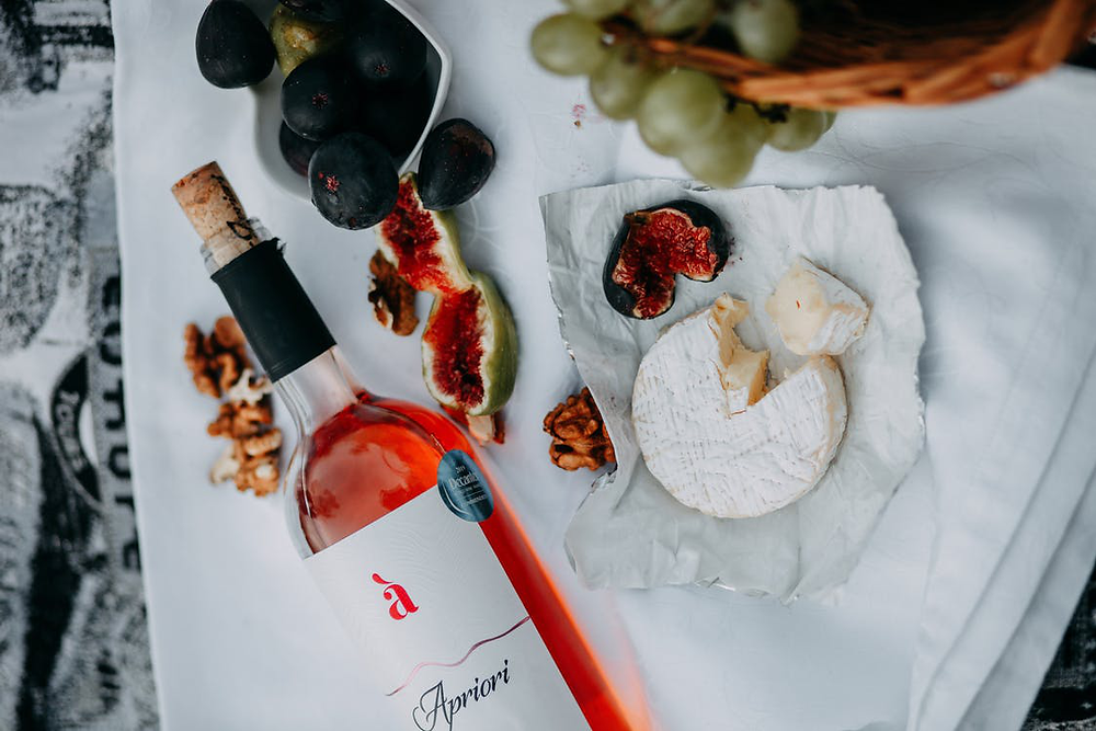 A bottle of wine with fruits and cheese.