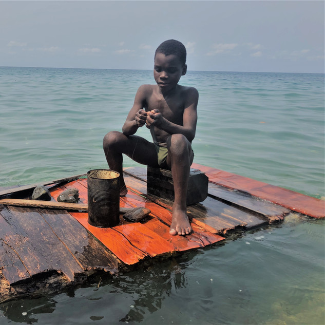 Boy fishing off Praia Camphaina