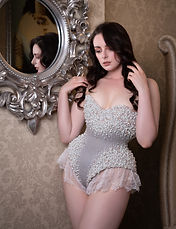 Liv is wearing a pearl encrusted corset body and lace tap pants
