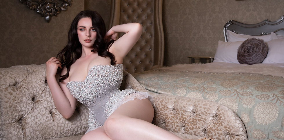 Liv is lounging on a chaise lounge whilst wearing a pearl encrusted corset body