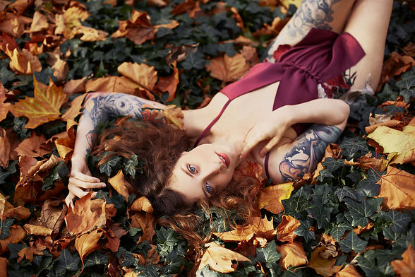 Palmyra laying on autumnal leaves, wearing a red playsuit