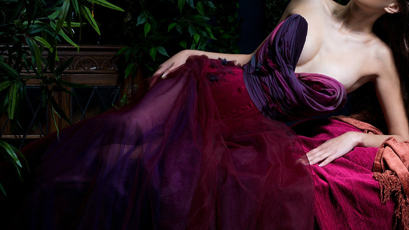 Kacie is wearing a red and purple draped over bust corset and red and purple tulle skirt