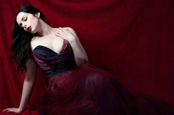 Liv is wearing a red and purple draped overbust corset with a red and purple tulle skirt