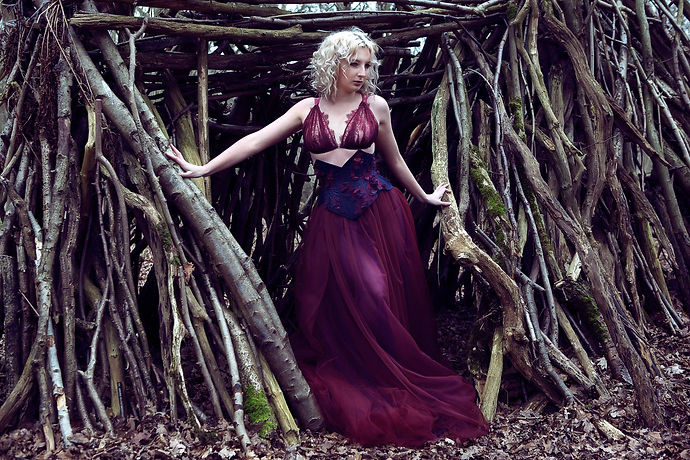 Cassie is wearing a red lace bralette, navy blue underbust and red and purple tulle skirt
