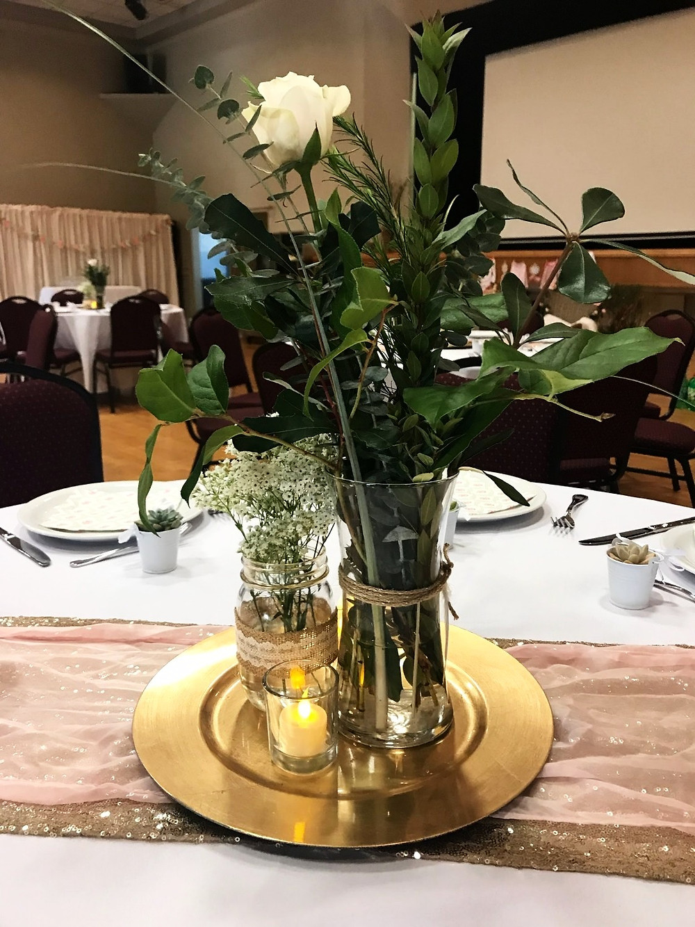 earthy center pieces with eucalyptus, white rose, mason jar, and gold chargers
