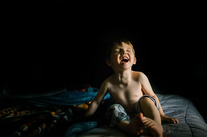 Boy laughing on bed