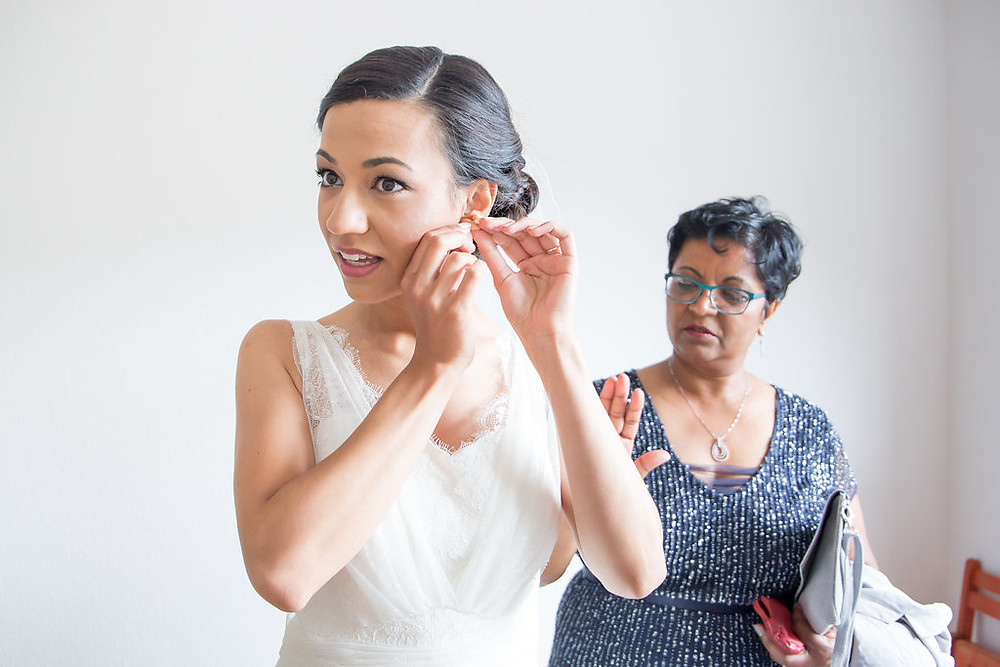 Sarina putting earrings are while her Mom is checking to make sure everything is perfect with her daughter