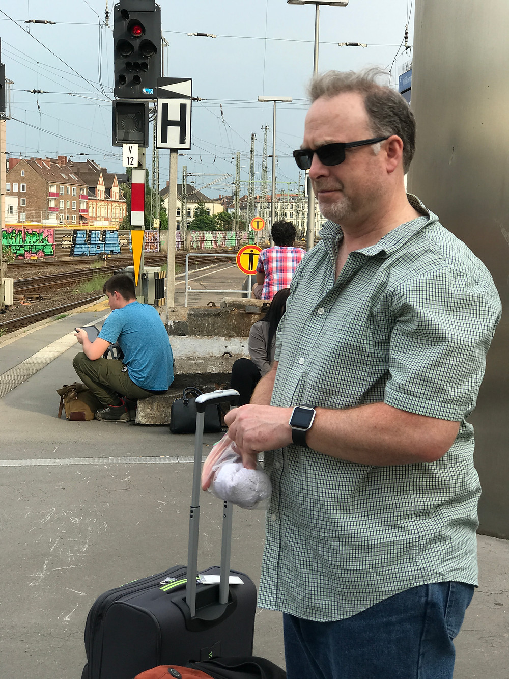 Pat standing guard with our bags at the Hanover Germany Train station while I'm walking around taking pictures of people and trains at this German Train station.