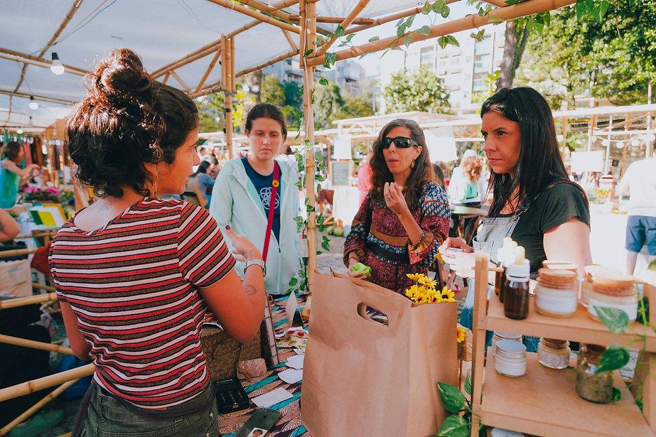Empreendedora vegana oferece amostras de seus produtos para três clientes na melhor e maior feira vegana do Rio de Janeiro. Ela vende produtos naturais, entre cosméticos naturais e outros itens. Ela está em uma barraca de bambu linda. É a força do empreendedorismo feminino.