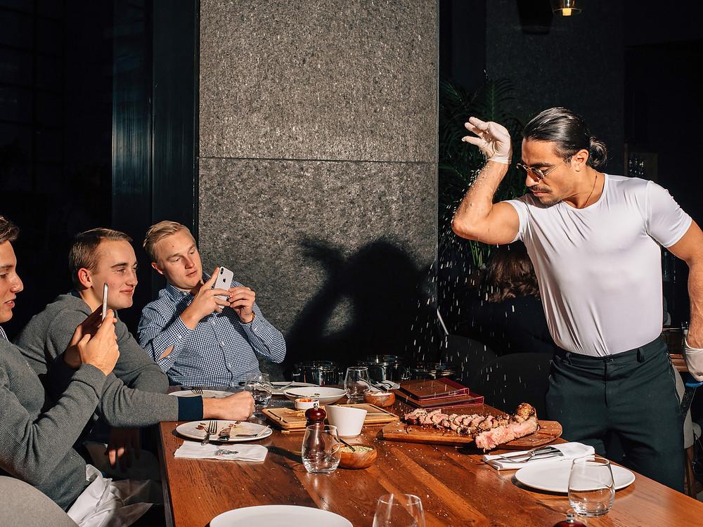 Salt Bae, o açougueiro turco que virou sensação na internet, joga sal sobre um pedaço de carne servido para três clientes europeus que filmam com seus celulares. Carne e masculinidade tóxica. A política sexual da carne.