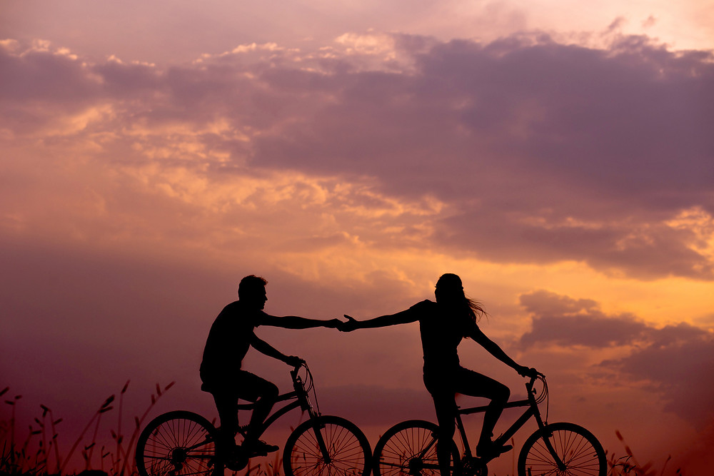 Couple riding bikes and holding hands