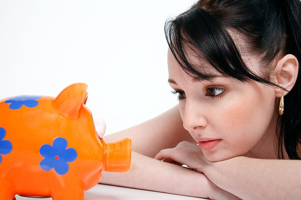 Young woman staring at piggybank