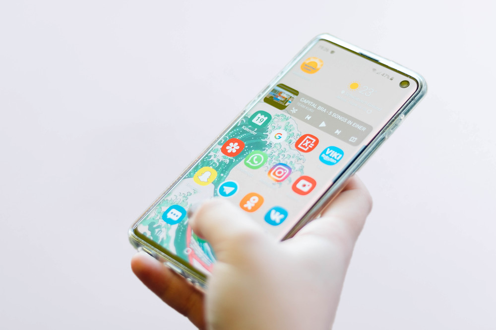 Person holding phone with apps