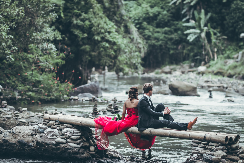 Well-dressed man and woman sitting on a log