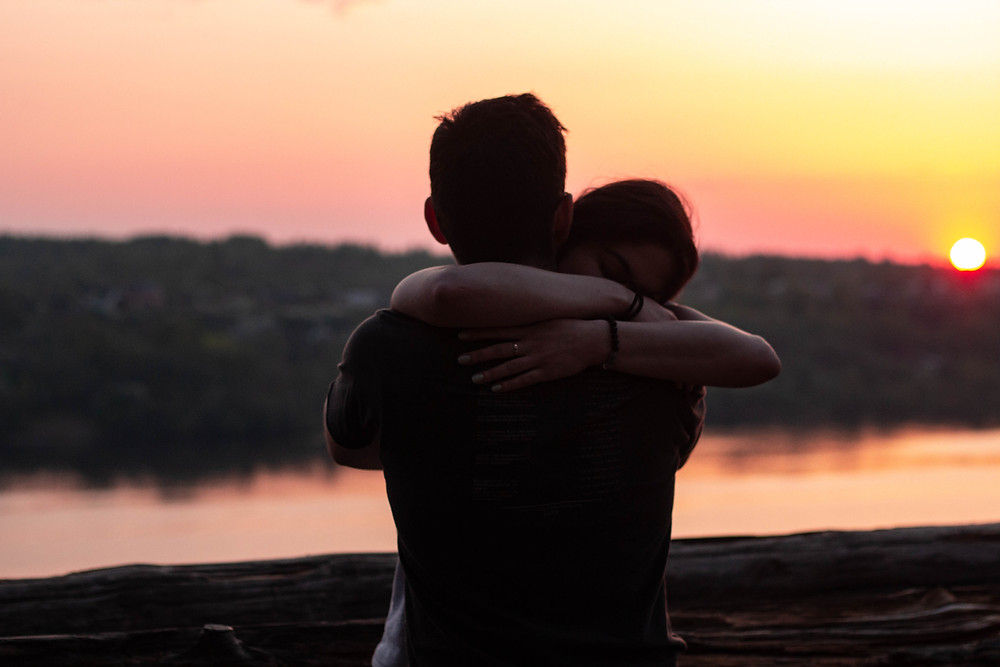 Couple hugging in a sunset