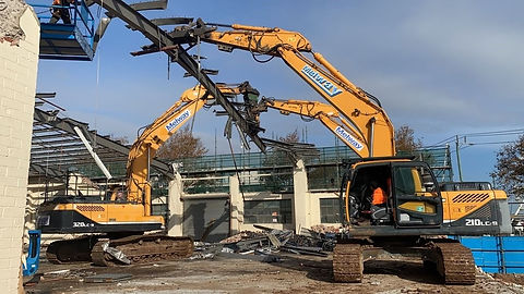 Three Melway Demolition Excavators in the process of bringing down a steel beam on a commercial demolition site in Melbourne