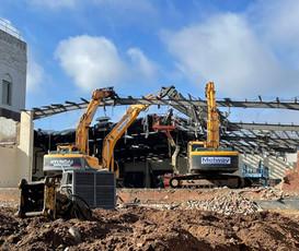 3 demolition machines demolishing steel beams