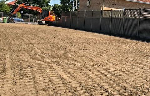A completed demolition site in Melbourne suburbs with the demolition excavator in the background. Clear, flat, track rolled demolition site, ready to build on