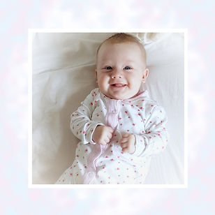 A smiling baby girl lays on her back with her hands resting on her tummy. She wears a white sleepsuit with pink flowers.