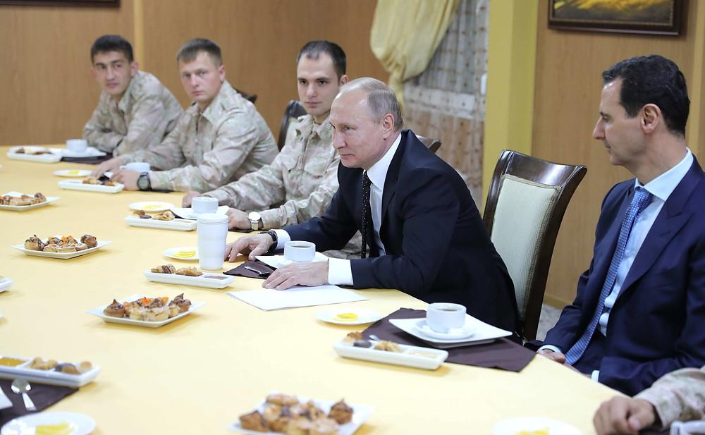 פוטין עם בשאר אל-אסד וחיילים רוסים בבסיס חיל האוויר חמיימים שבסוריה, בדצמבר 2017