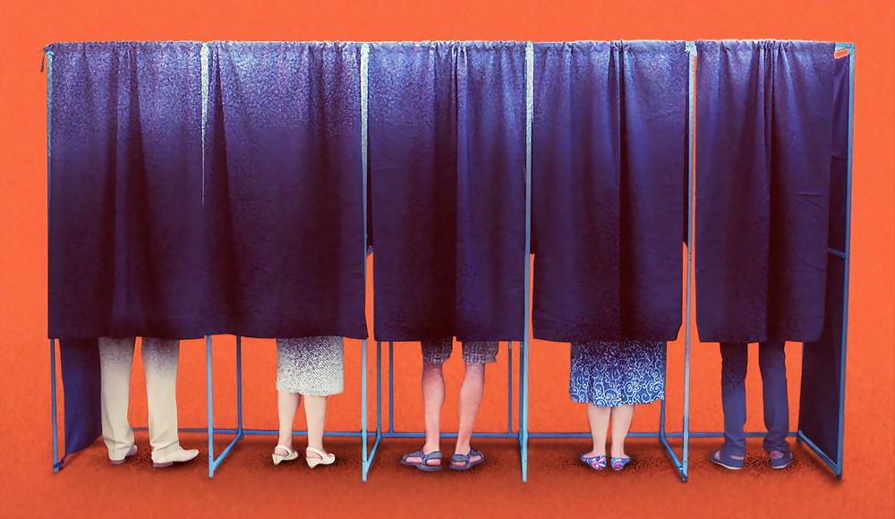 Menschen stehen in Wahlkabinen