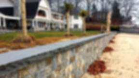 Stone veneer retaining wall with Rock face bluestone cap, project in Northport NY