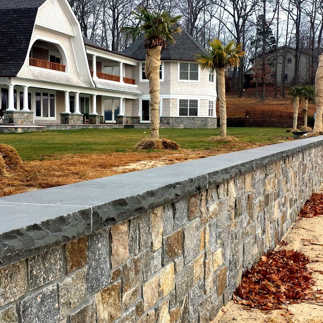 Natural stone veneer retaining wall with bluestone wall cap