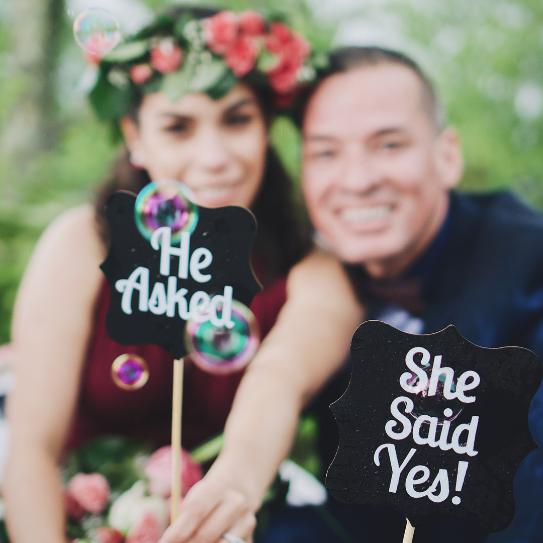 happy-engaged-couple-holding-signs-that-