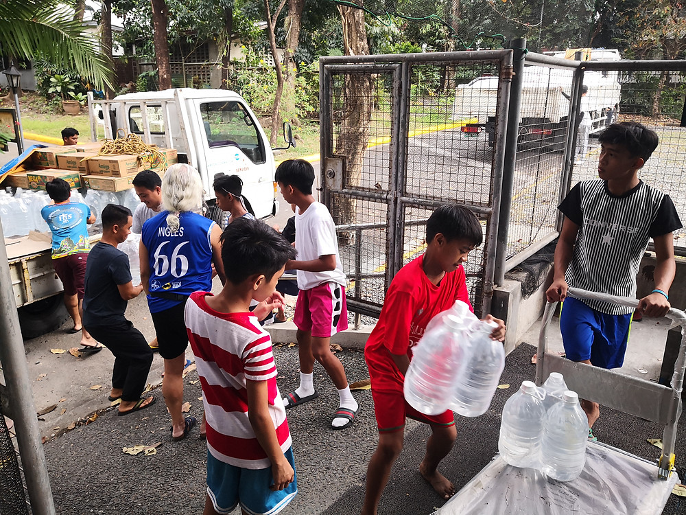 """Coach Eric and the """"Blue Guards"""", helping out in receiving donations at Richie Fernando Covered Courts in Ateneo de Manila"""