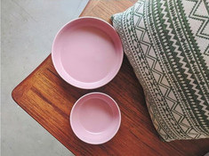Flatlay of pink bowls and a green aztec patterned cushion