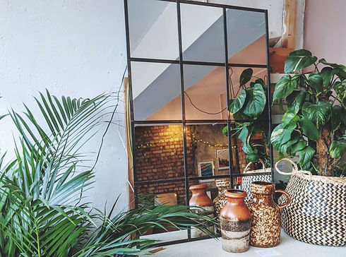 Window frame inspired mirror with vases and plants