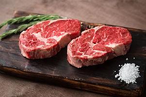 Two fresh raw rib-eye steak on wooden Bo