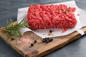 Minced meat on butcher paper with basil