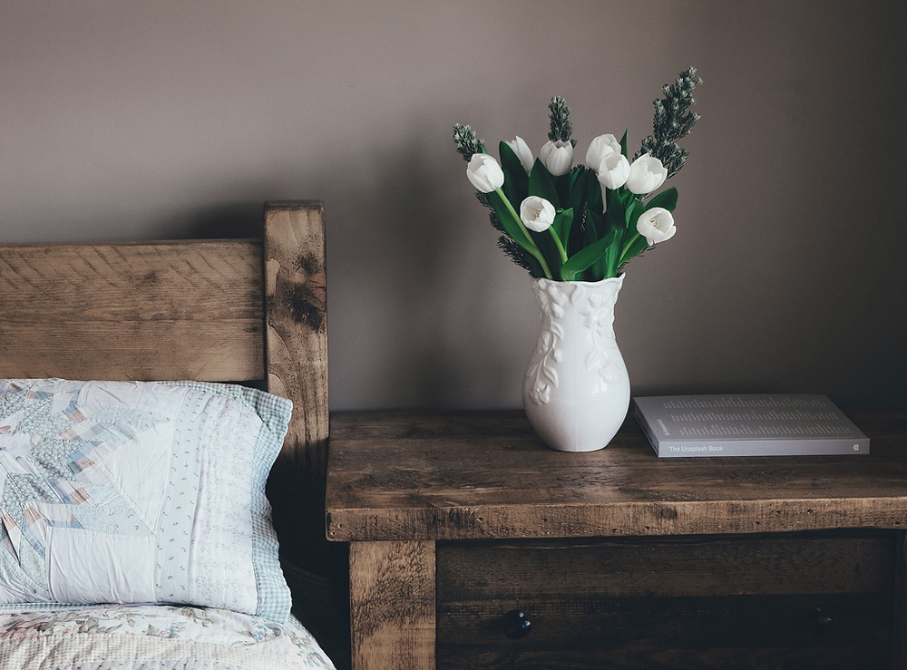 Wooden bedside table with white flowers.