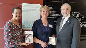 L-R: Briohne Sykes (scriptwriter), Dee Handyside (composer) hand over the Silk Rags Project to Professor Ian Brown, Chief Executive of the Australian Cancer Research Foundation (ACRF)
