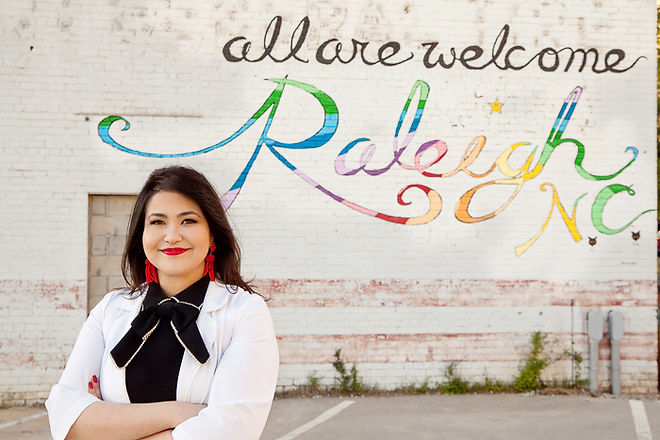 Andrea Arnold, owner of Haute Hair Removal & Aesthetics of Cary NC, standing in front of mural in Downtown Raleigh