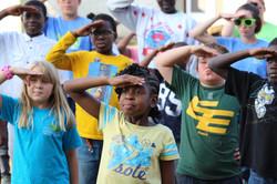 kids at camp saluting