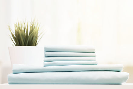 Closeup of blue clean bedding on a blurr