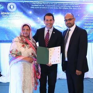 MP Peter Fonseca awarding a certificate to the in charge, Rashida Jilani, Azeemia Spiritual & Healing Centre Canada on the successful organization of Adam Day 2017