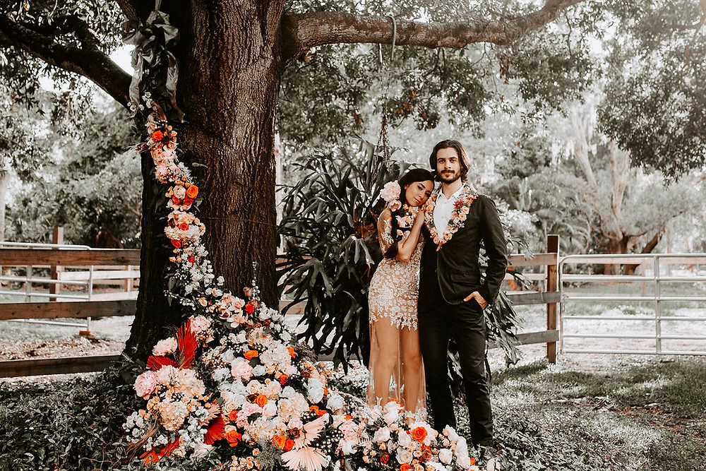 Couple embracing with a gorgeous flower installation flowing down a tree