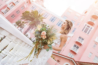 Beautiful Boho Flowing Bride Bouquet with Hanging Amaranthus Peach Roses Kale Eucalyptus Palm Fronds in front of Don CeSar Hotel St. Pete Beach Tampa Bay Florida Julie Terry Photography Lemon Drops Weddings & Events