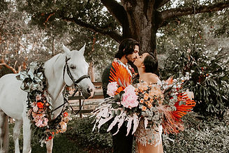 Rustic Boho Chic Style Floral Bouquet & Garland for Horse in Warm Pink Orange Coral Rust Flowers while Couple is Kissing Under a Tree Mari Sabra Photography Lemon Drops Weddings & Events