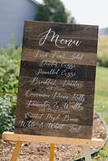 This is an image of a wooden sign with a menu written on it.