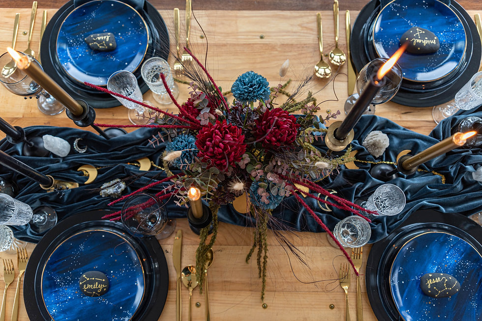 This is a photo of a table set for four with a large floral centerpiece in the middle and lighted candles.