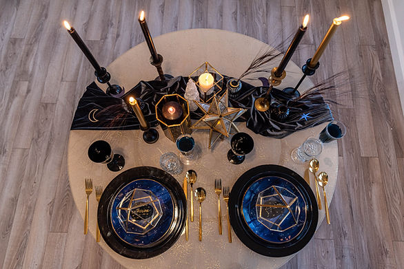 This photo is of a table set for two with candles, plates and celestial decor.