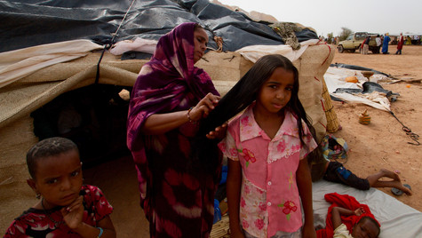 A mother brushes her daughter's hair, Mentao refugee camp, Burkina Faso, 2014