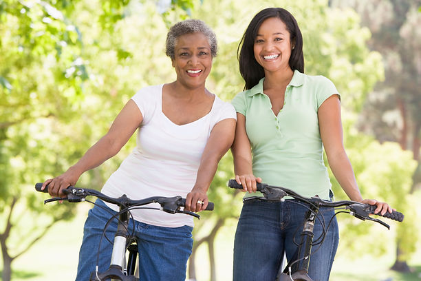 two-women-on-bikes-outdoors-smiling_Bt30