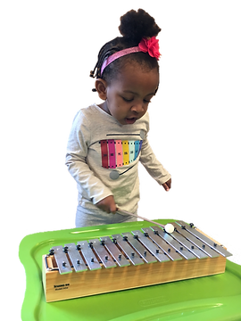 toddler plays drum Suzuki early childhood music class