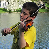 violin student playing music in the park